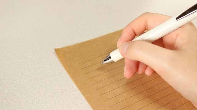 ペンを持ち紙に文字を書いている
